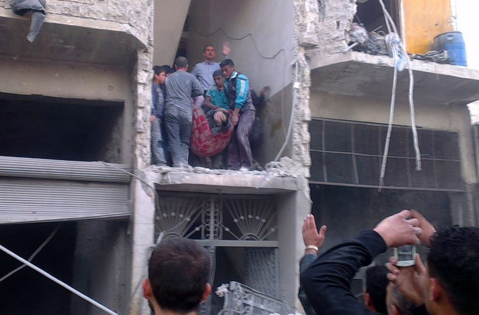 Syrian citizens carry an injured man from a damaged building that was hit by a Syrian forces airstrike, on the al-Marjeh neighborhood, of Aleppo, Syria, Tuesday, March 19, 2013. (AP / Aleppo Media Center, AMC)
