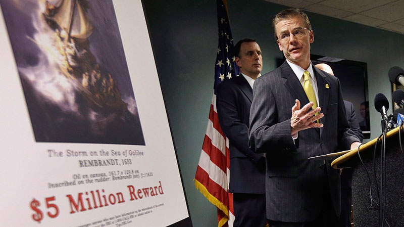 Federal Bureau of Investigation (FBI) Special Agent in Charge Richard DesLauriers, right, stands next to a poster that shows a Rembrandt painting and a reward while facing reporters during a news conference at FBI headquarters in Boston, Monday, March 18, 2013. (AP / Steven Senne)