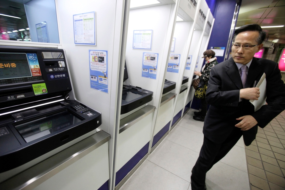 A depositor leaves after checking his account through an automated teller machine at a subway station as the bank's computer networks was paralyzed in Seoul, South Korea, Wednesday, March 20, 2013. (AP Photo/Ahn Young-joon)