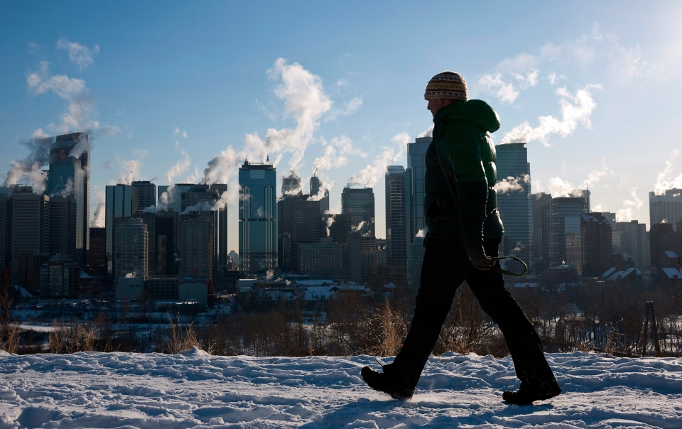 A man walks past a the Calgary, Alta., skyline as steam rises from downtown office towers Monday, Jan. 31, 2011. (Jeff McIntosh / THE CANADIAN PRESS)