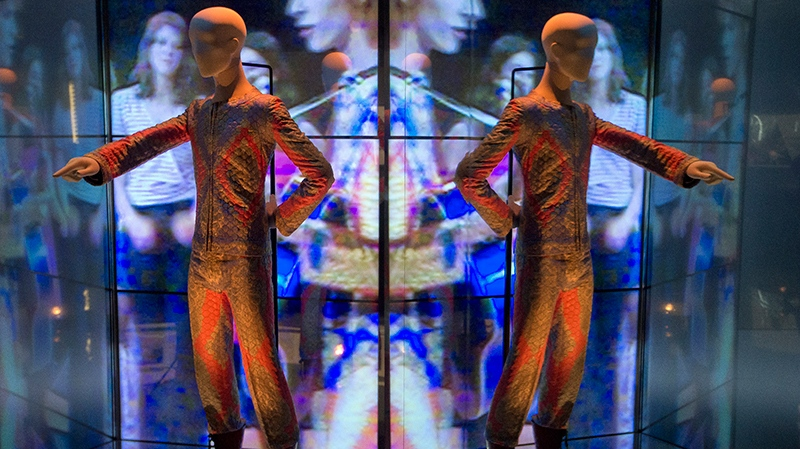 A reflection of the costume that David Bowie wore as Ziggy Stardust on tour and during a performance of 'Starman' on British pop music show Top of The Pops, is photographed as part of a retrospective David Bowie exhibition, entitled David Bowie Is, at the V&A Museum in west London, Wednesday, Mar. 20, 2013. (Photo by Joel Ryan/Invision/AP)
