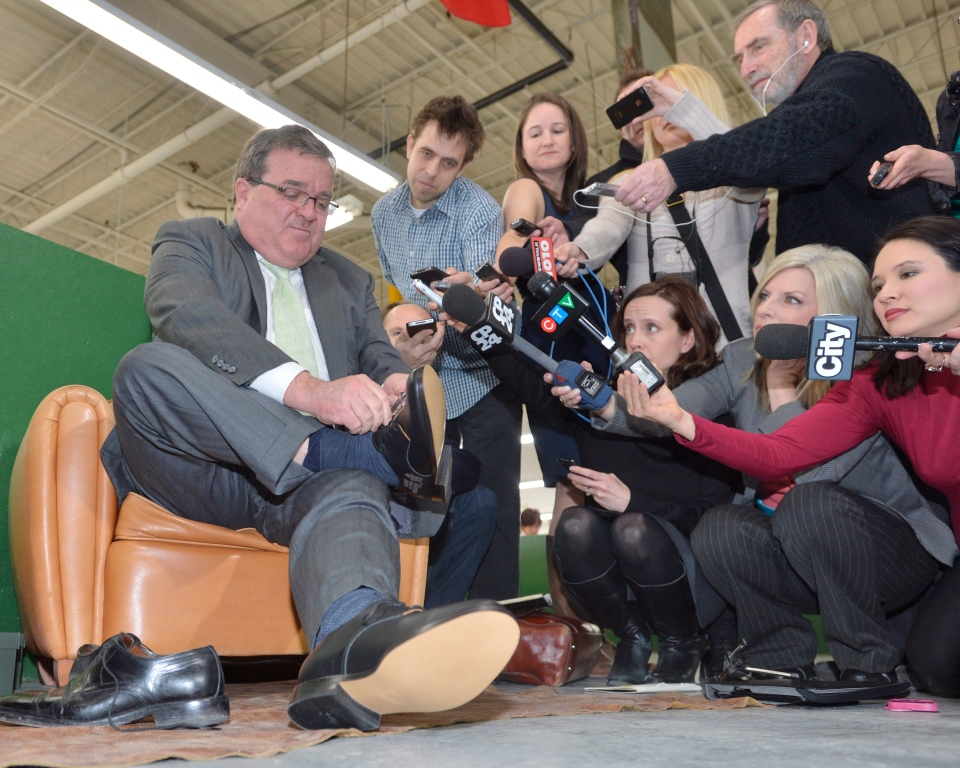 Finance Minister Jim Flaherty tries on a new pair of shoes at the Roots factory in Toronto, Wednesday, March 20, 2013. Flaherty is set to table the federal budget in the House of Commons on Thursday. (Nathan Denette / THE CANADIAN PRESS)