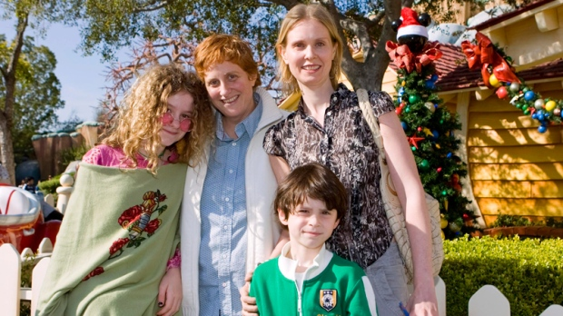 In this image released by Disneyland, actress Cynthia Nixon, right, poses with her daughter Samantha, 12, left, her partner Christine Marinoni and son Charlie, 6, foreground, outside Mickey Mouse's home in Toontown during a visit to Disneyland in Anaheim, Calif., Wednesday, Dec. 31, 2008.