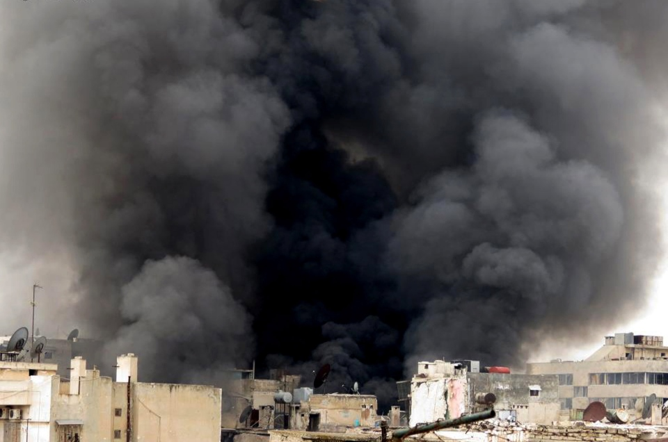 Black smoke rises from buildings due to government forces shelling, in Aleppo, Syria, Tuesday March 19, 2013. (Aleppo Media Center / AMC)