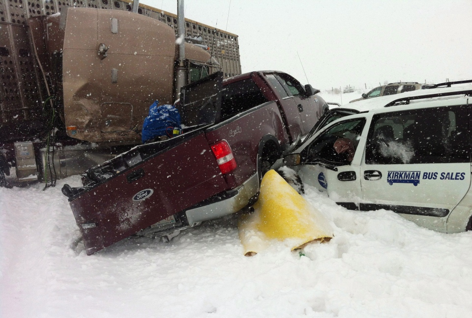 A pickup truck is sandwiched between two vehicles as more than 100 people have been injured following a multi-vehicle crash in snowy conditions on Highway 2 south of Edmonton on Thursday, March 21, 2013. (Derek Fildebrandt / THE CANADIAN PRESS)