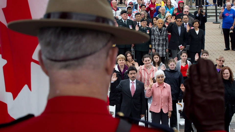 A Royal Canadian Mounted Police officer raises his hand as a group of 60 people take the oath of citizenship during a special Canada Day citizenship ceremony in Vancouver, B.C., on Sunday, July 1, 2012. (Darryl Dyck / THE CANADIAN PRESS)