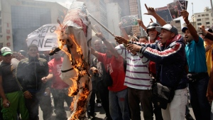 Supporters of Venezuela's late President Hugo Chavez burn a sign taken from opposition student protesters a few blocks from the electoral commission in Caracas, Venezuela, Thursday, March 21, 2013. (AP / Ariana Cubillos)
