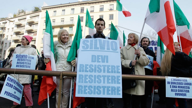 Dozens of Italian Premier Silvio Berlusconi supporters wave Italian flags in a demonstration across the street from the Milan courthouse entrance in Milan, Wednesday, Feb. 9, 2011. (AP / Luca Bruno)