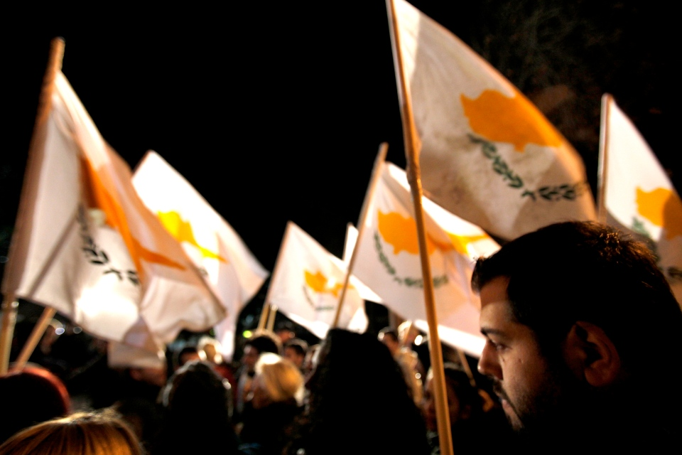 Protesters hold Cyprus' flags during a rally outside the parliament in capital Nicosia, Cyprus, Friday, March 22, 2013.  (AP Photo/Petros Karadjias)