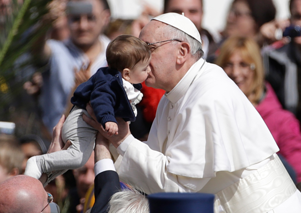 Pope Francis kisses a child as he leaves after celebrating his first Palm Sunday Mass, in St. Peter's Square, at the Vatican, Sunday, March 24, 2013. (AP / Andrew Medichini)