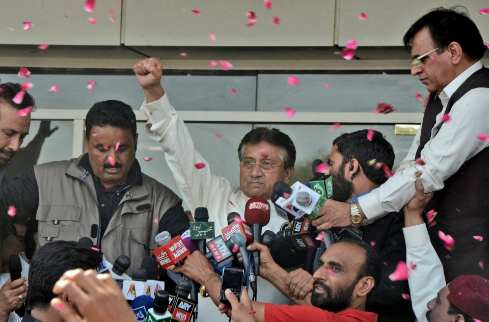 Former Pakistani President Pervez Musharraf, centre, gestures to his supporters, unseen, upon his arrival to Karachi airport, Pakistan, Sunday, March 24, 2013. (AP / S.I. Ali)