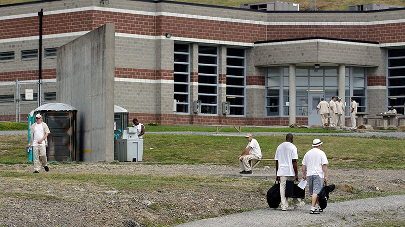 Inmates walk in the yard at the maximum-security Mount Olive Correctional Center in Mount Olive, W. Va on Tuesday, July 3, 2012.  (AP / Steve Helber)