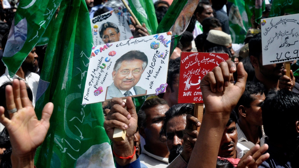 Supporters of Former Pakistani President Pervez Musharraf, hold placards showing him, upon his arrival to Karachi airport, Pakistan, Sunday, March 24, 2013. (AP / S.I. Ali)