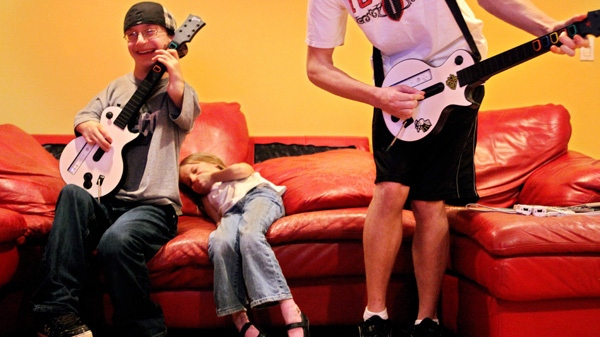 "In this Jan. 20, 2010 file photo, A.J. Leitch, 18, left, plays ""Guitar Hero"" with his cousins Kamarina Hewett, 6, and Andrew Engles, 16, in Seattle. (AP Photo/The Seattle Times, Erika Schultz)"
