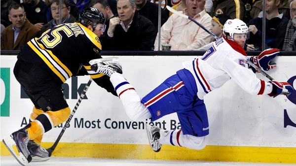 Benoit Pouliot drops to the ice after contact with Boston Bruins defenceman Johnny Boychuk Wednesday, Feb. 9, 2011. (AP Photo/Elise Amendola)