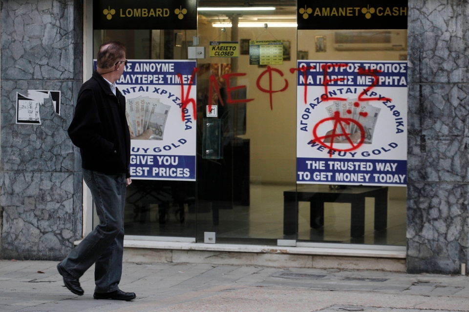 """A man passes a sprayed entrance of a store that buys gold which reads in Greek """"thieves"""" in Nicosia, Cyprus, Monday, March 25, 2013. (AP / Petros Giannakouris)"""