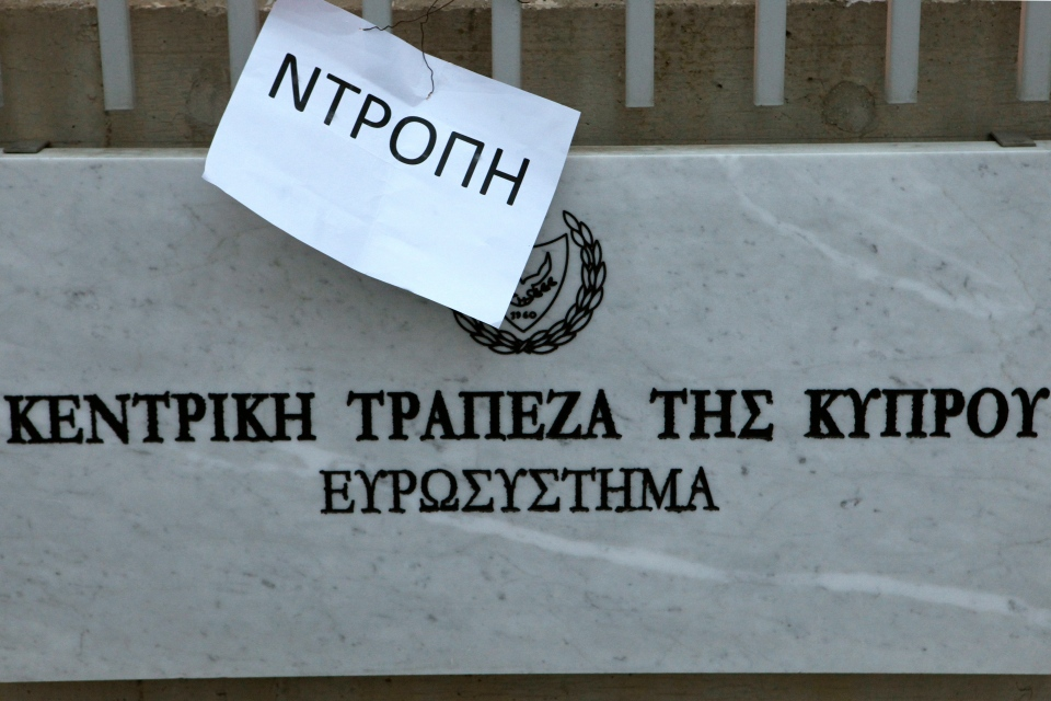 "A plaque at the entrance of Cyprus central Bank reads ""Central bank of Cyprus, Eurosystem"" in Greek, as a poster placed by employees from the Bank of Cyprus reads ""shame"", during a protest outside of Cyprus central bank in Nicosia, Cyprus, Tuesday, March 26, 2013. (AP / Petros Karadjias)"