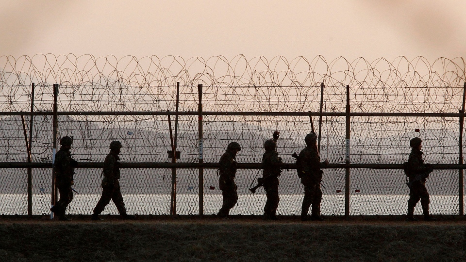 South Korean army soldiers patrol along a barbed-wire fence near the border village of Panmunjom in Paju, South Korea, Tuesday, March 26, 2013. (AP / Ahn Young-joon)