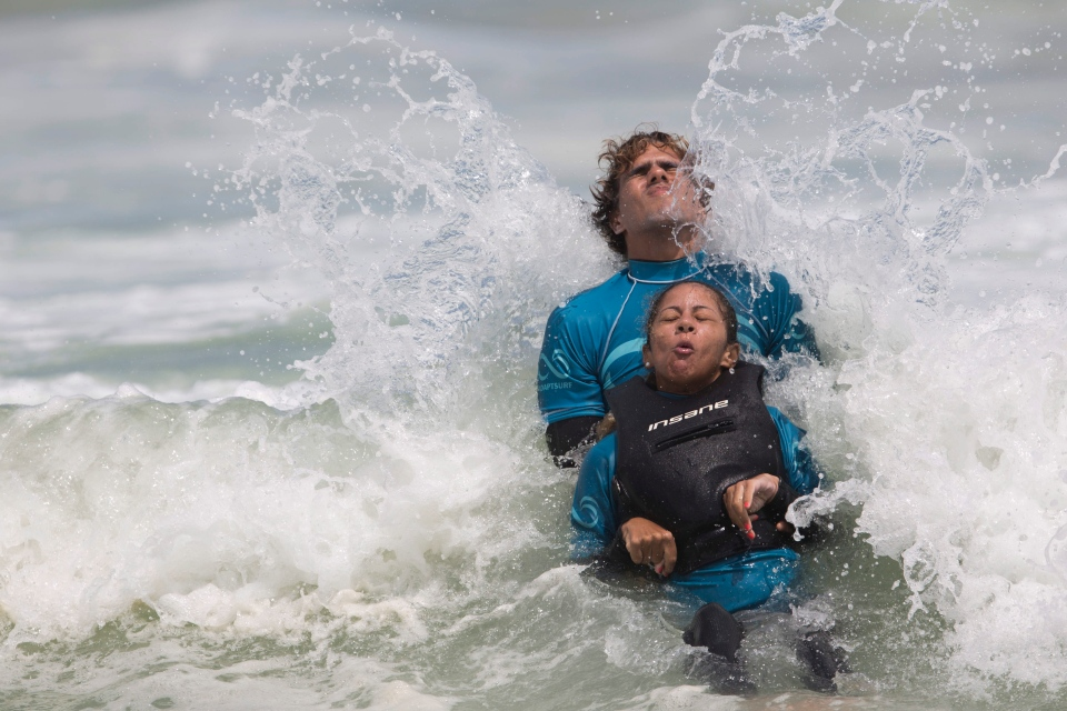 Monique Oliveira is aided by an AdaptSurf volunteer as a wave breaks at Barra da Tijuca beach in Rio de Janeiro, Brazil. (AP Photo/Felipe Dana)