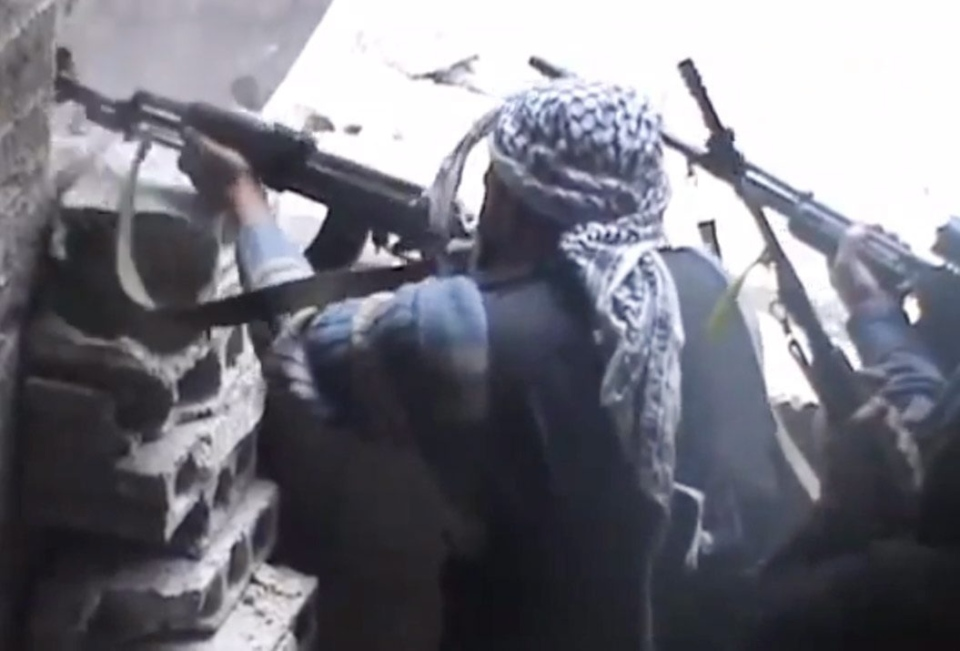 Free Syrian Army fighters aim their weapons during clashes in the countryside of Damascus, Syria on Monday, March 25, 2013. (Ugarit News via AP video)