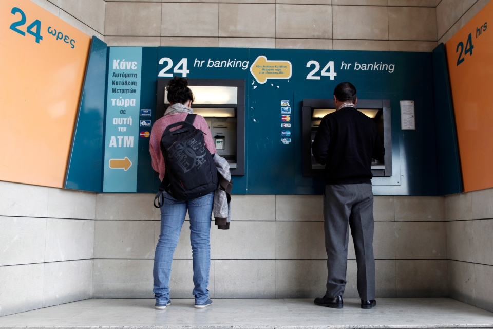 People use ATMs outside a closed branch of the Bank of Cyprus in Nicosia, Cyprus, Wednesday, March 27, 2013. (AP / Petros Giannakouris)