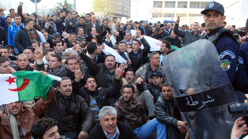 Algerian protesters holding an Algerian flag as they gather in front of Police officers during a demonstration in Algiers, Algeria, Saturday Feb. 12, 2011. (AP / Sidali Djarboub)