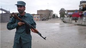 An Afghan police man stands guard on the road leading to the Kandahar police headquarters in Kandahar south of Kabul, Afghanistan, Saturday, Feb, 12, 2011. (AP / Allauddin Khan)