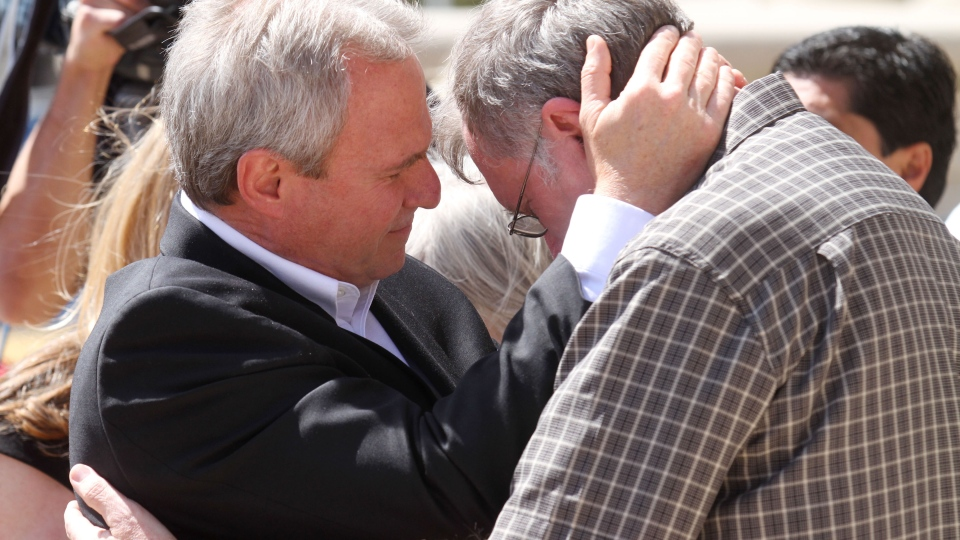 Michael Morton, left, and Dale Norwood embrace on the steps of the Tom Green County Courthouse Wednesday, March 27, 2013 in San Angelo, Texas after a guilty verdict was handed down to Norwood's brother, Mark Norwood, was found guilty of the 1986 murder of Morton's wife, Christine.  (AP/San Angelo Standard-Times, Patrick Dove)