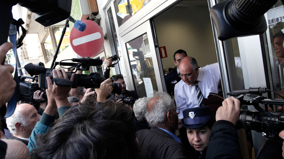 A bank employee opens the door of a Laiki bank branch in Nicosia, Thursday, March 28, 2013. (AP / Petros Giannakouris)