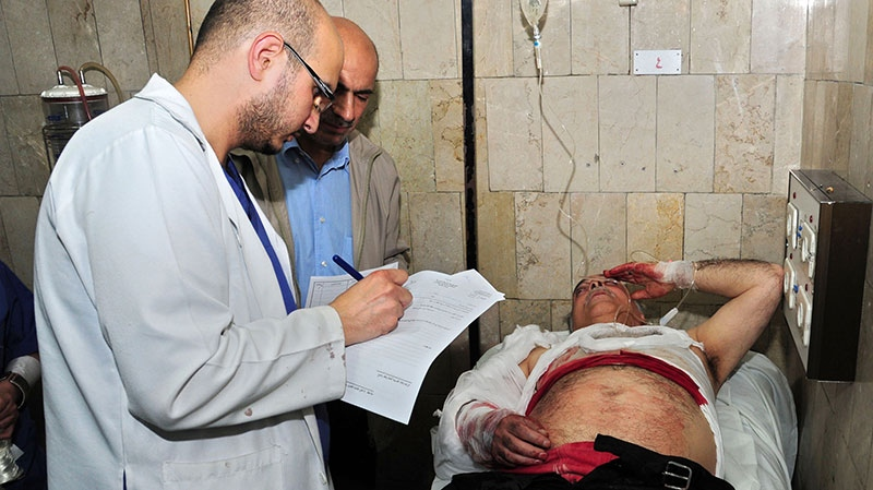 A Syrian doctor, left, treats an injured man, right, who was wounded at the open-air cafeteria at Damascus University in the central Baramkeh district, in Damascus, Syria, Thursday, March 28, 2013. (SANA)