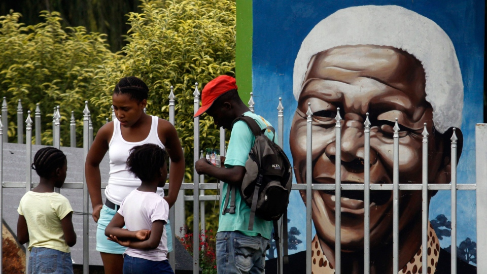 Visitors gather in front of a portrait of former president Nelson Mandela, in a Park in Soweto, South Africa, Thursday, March, 28, 2013. (AP / Denis Farrell)
