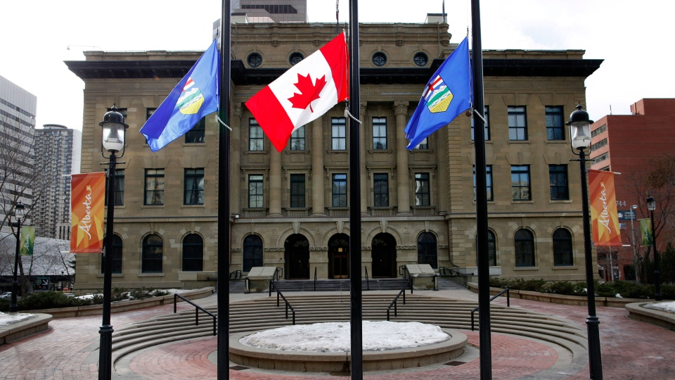 The flags of Alberta and Canada fly at half-mast in front McDougall Centre, where former premier Ralph Klein had his Calgary office, in Calgary on Friday, March 29, 2013. (Jeff McIntosh / THE CANADIAN PRESS)