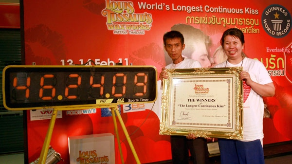 Laksana Tiranarat, right, and husband Ekkachai pose with a certificate after winning the World's Longest Continuous Kiss contest and set a new record at 46.24.09 hours in Pattaya, southeastern Thailand Tuesday, Feb. 15, 2011. (AP Photo / Apichart Weerawong)