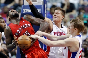 Toronto Raptors center Amir Johnson (15) is fouled by Detroit Pistons forward Kyle Singler, right, while trying to shoot as Detroit forward Jonas Jerebko, second from right, of Sweden, helps defend the basket in the second half of an NBA basketball game on Friday, March 29, 2013, in Auburn Hills, Mich.  (AP / Duane Burleson)