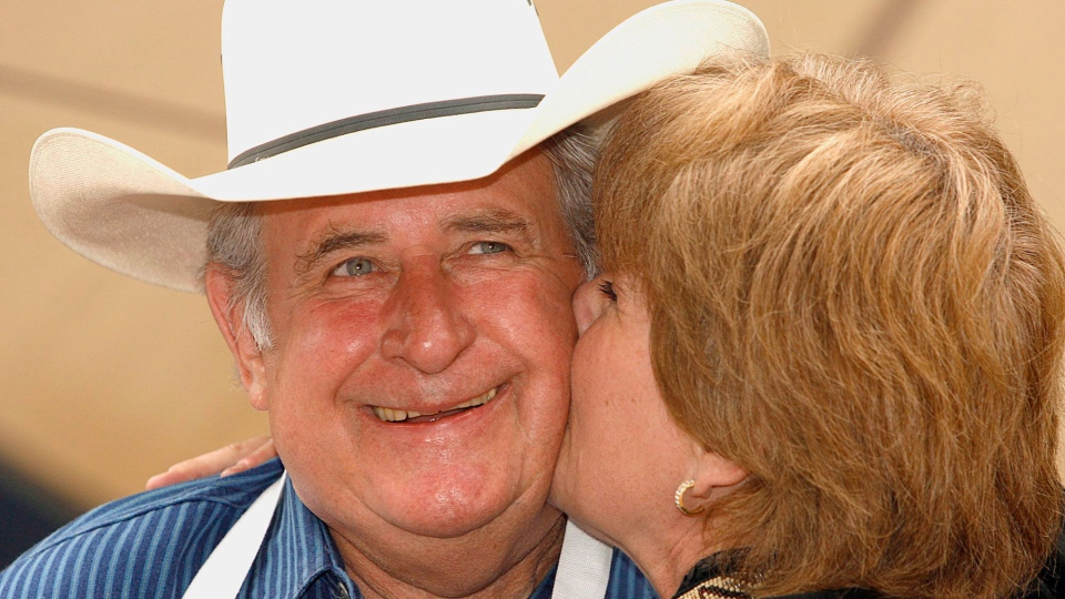 Then-Alberta premier Ralph Klein gets a kiss at the Annual Ralph Klein Pancake Breakfast in Calgary, on July 10, 2006. (Larry MacDougal / THE CANADIAN PRESS)