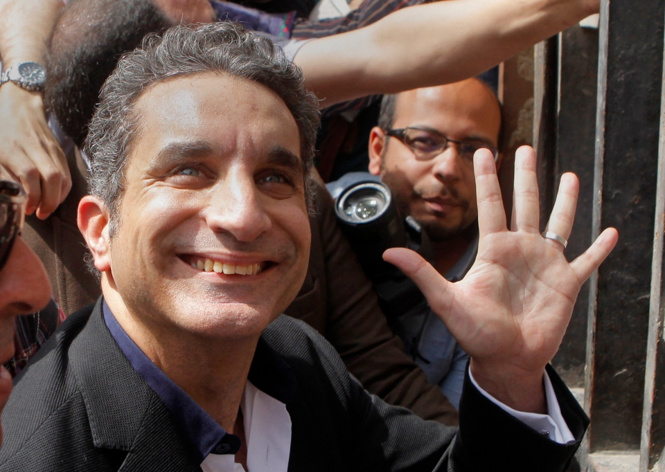 Popular Egyptian television satirist Bassem Youssef, who has come to be known as Egypt's Jon Stewart, waves to his supporters as he enters Egypt's state prosecutors office to face accusations of insulting Islam and the country's Islamist leader in Cairo, Egypt, Sunday, March 31, 2013. (AP / Amr Nabil)