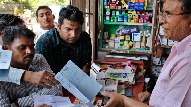 An Indian shopkeeper receives prescriptions to prepare medicines at his store in Allahabad, India, Monday, April 1, 2013. (AP / Rajesh Kumar Singh)
