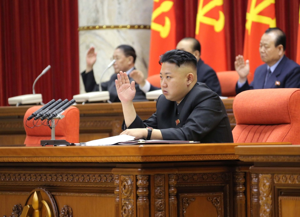 North Korean leader Kim Jong Un raises his hand with other officials to adopt a statement during a plenary meeting of the central committee of the ruling Workers' Party in Pyongyang, North Korea, Sunday, March 31, 2013. (KCNA via KNS)