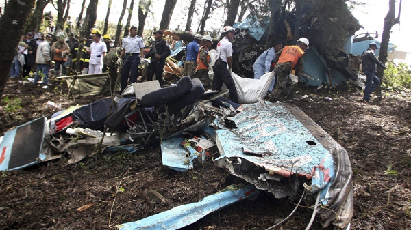 Rescue workers remove bodies from the wreckage of a small commercial airplane after it crashed near the town of Las Mesitas on the outskirts of the capital city of Tegucigalpa, Honduras Monday Feb. 14, 2011. (AP Photo/Fernando Antonio)