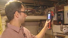 Eric Bjornson examines a home for signs of heat loss.