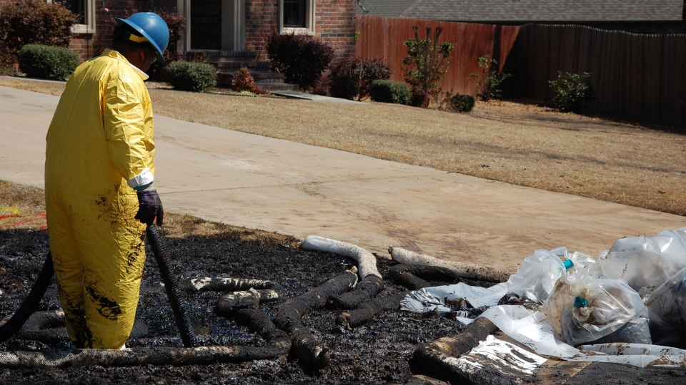 A worker cleans up oil in Mayflower, Ark., on Monday, April 1, 2013, days after a pipeline ruptured and spewed oil over lawns and roadways. (AP / Jeannie Nuss)