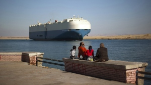 A cargo ship transits the Suez Canal en route from the Mediterranean Sea to the Gulf of Suez at the city of Suez, Egypt, Wednesday, Feb. 2, 2011. (AP / Emilio Morenatti)