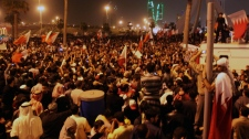Bahraini anti-government protesters wave flags in a demonstration at the Pearl roundabout in Manama, Bahrain, Wednesday, Feb. 16, 2011. (AP / Hasan Jamali)
