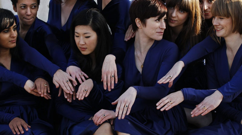 A group of students from the Royal College of Art pose for photographs wearing Kate Middleton style engagement outfits they made themselves and engagement rings outside Buckingham Palace in London, Wednesday, Jan. 19, 2011. (AP Photo/Matt Dunham)