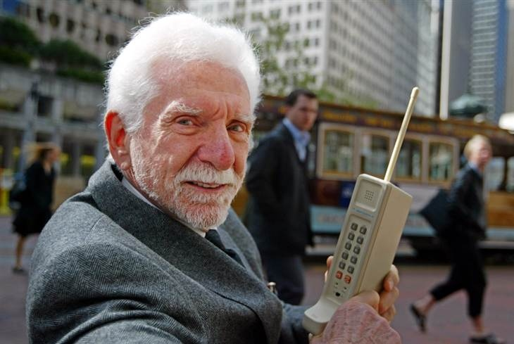 Martin Cooper, chairman and CEO of ArrayComm, holds a Motorola DynaTAC, a 1973 prototype of the first handheld cellular telephone on Market Street in San Francisco, Wednesday April 2, 2003. (AP / Eric Risberg)