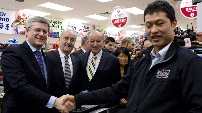 Prime Minister Stephen Harper, standing with Minister of State for Seniors Julian Fantino and Justice Minister Rob Nicholson, shakes hands with David Chen, right, at his grocery store in Toronto on Thursday Feb. 17, 2011. Chris Young / THE CANADIAN PRESS)