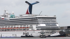 Tug boats maneuver around the Carnival cruise ship Triumph as she rests against a dock on the east side of the Mobile River after becoming dislodged from its mooring at BAE Shipyard during high winds  in Mobile, Ala. Wednesday, April 3, 2013. (AP / AL.com, Bill Starling)