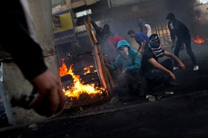 Palestinians clash with Israeli forces, not pictured, in the West Bank city of Hebron, Thursday, April 4, 2013. (AP / Bernat Armangue)
