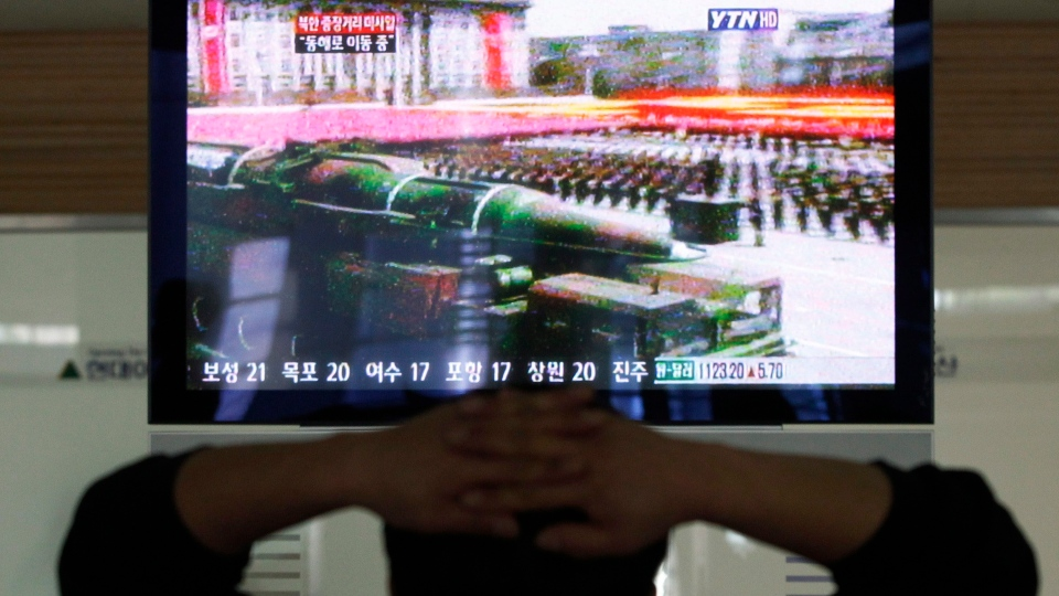 A South Korean man who is waiting to head to the North Korean city of Kaesong, watches a news program airing file footage of a North Korean rocket displayed during a military parade at the customs, immigration and quarantine office in Paju, South Korea, near the border village of Panmunjom, Thursday, April 4, 2013. (AP / Ahn Young-joon)