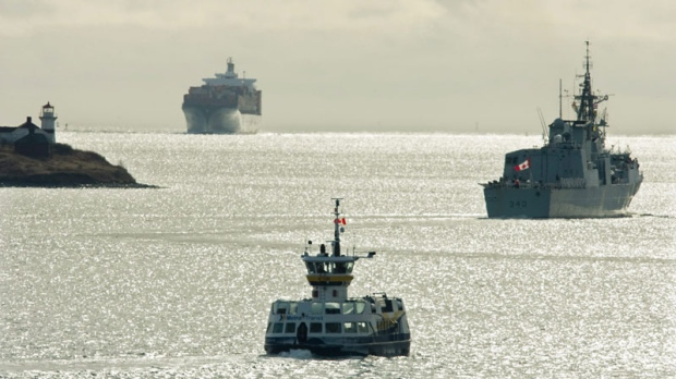 The Halifax-class frigate HMCS St. John's, right, heads past a ferry as a container ship arrives in Halifax harbour on Tuesday, Jan. 25, 2011. (THE CANADIAN PRESS/Andrew Vaughan)